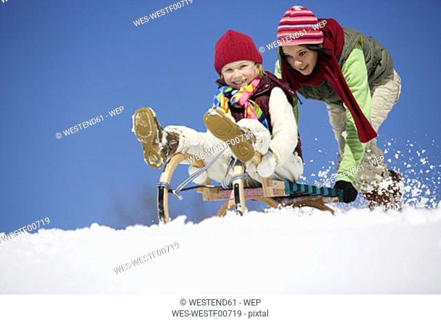 Austria, teenage girl (16-17) pushing girl (6-7) on sledge, smiling, low angle view