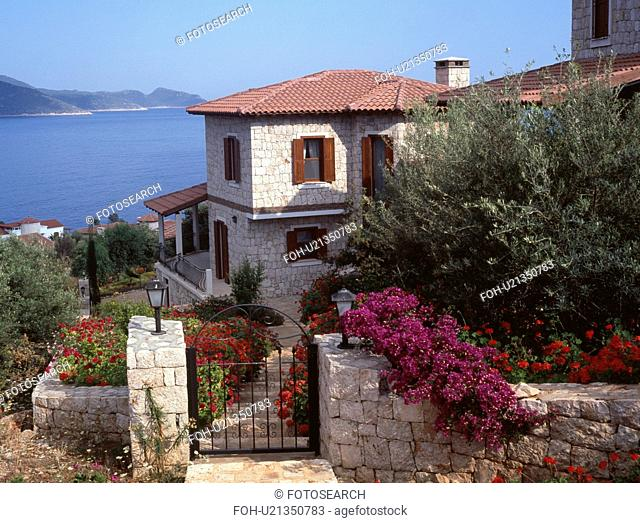 Metal gate and purple bougainvillea on wall in front of Turkish coastal villa with view of the ocean