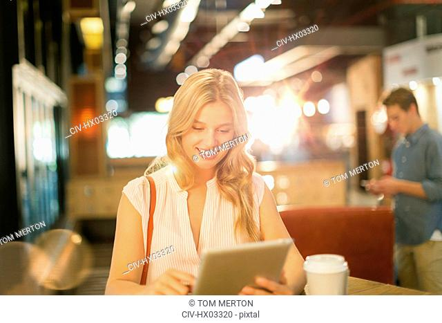 Smiling young woman using digital tablet and drinking coffee in cafe
