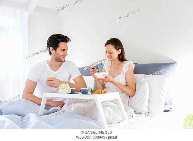 Couple in bed with breakfast tray
