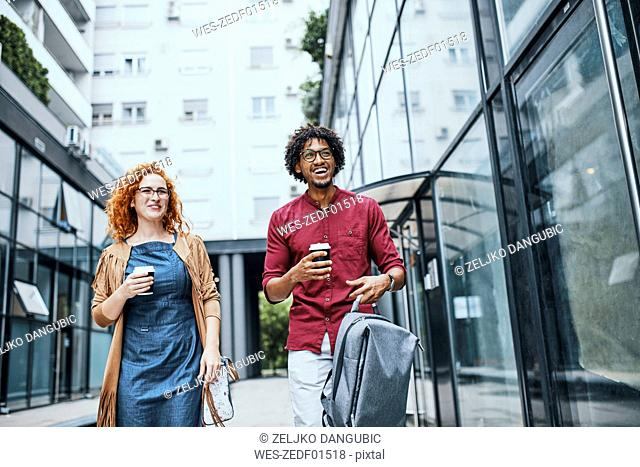 Colleagues walking together in the city, woman drinking coffee
