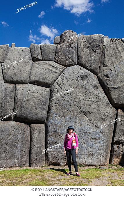 Female tourist giving scale to the massive walls of the Sacsayhuaman Incan fortress at Cusco, Peru