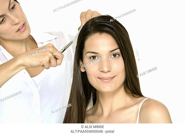 Woman having her hair cut by stylist, smiling at camera