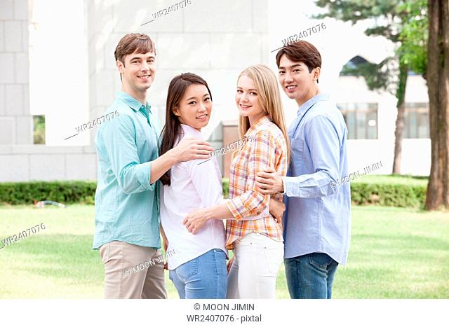 Back appearance of domestic students and international students in college putting their arms around each other outside on campus all looking back with a smile