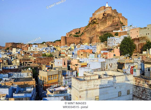 Cityscape of Jodhpur with traditional indigo blue and white painted houses and the 15th century Mehrangarh Fortress on the hilltop
