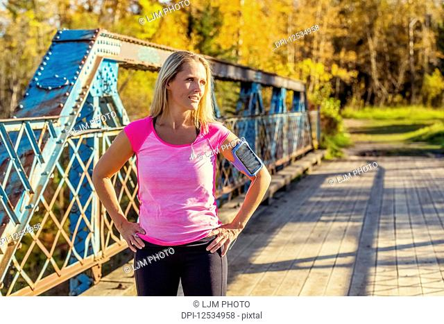 An attractive middle-aged woman pauses to rest on a bridge during a run on a beautiful warm fall evening in a city park; Edmonton, Alberta, Canada