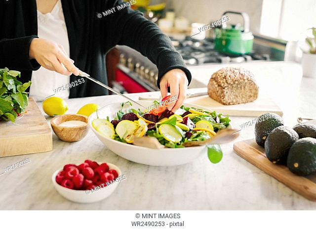 A woman in a kitchen preparing a salad dish with fresh vegetables