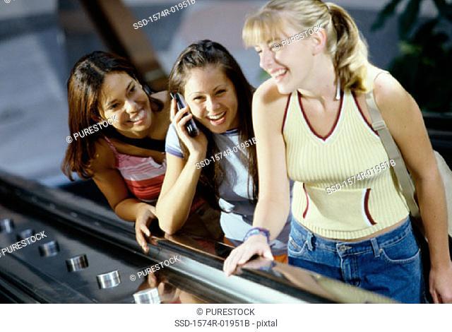 Three teenage girls standing on an escalator