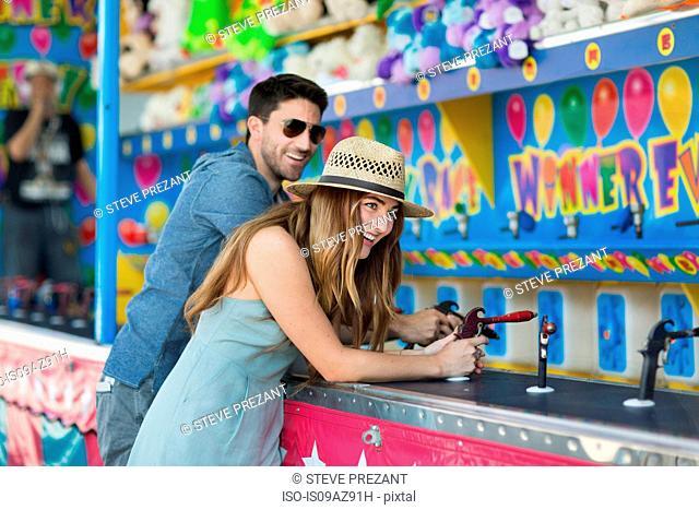 Couple at fairground shooting gallery, Coney island, Brooklyn, New York, USA