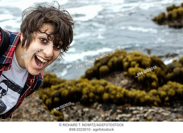 I teenage girl shows her excitement to be at the Point Lobos State Reserve, in Northern California