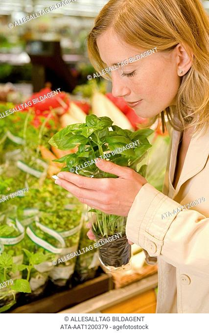 Woman taking a smell at basil