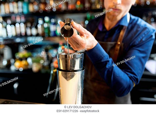 drinks, people and luxury concept - barman pouring alcohol from jigger into shaker and preparing cocktail at bar