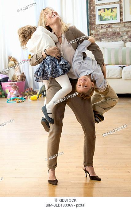 Caucasian working mother playing with children