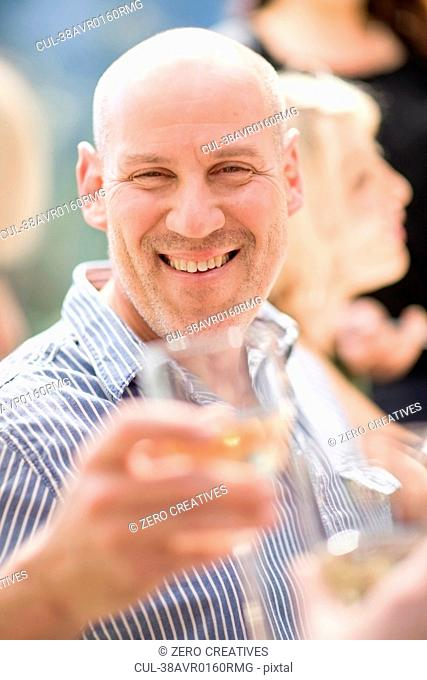 Smiling man with glass of wine outdoors