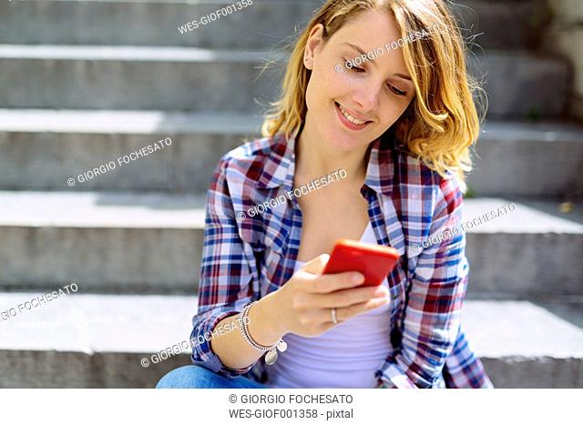 Portrait of smiling young woman sitting on stairs using smartphone