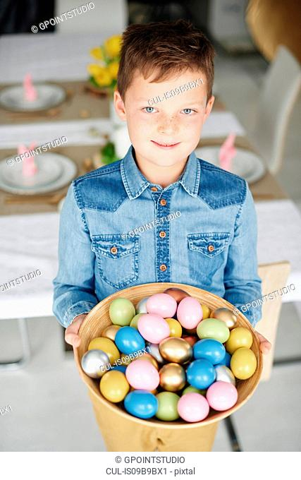 Portrait of boy holding bowl of colourful easter eggs