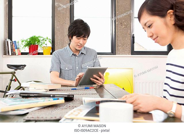 Young couple in sitting at desk in apartment