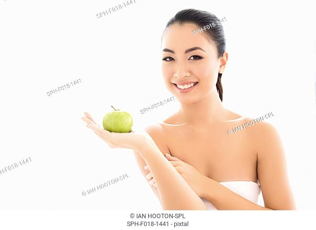 MODEL RELEASED. Young Asian woman holding apple, portrait