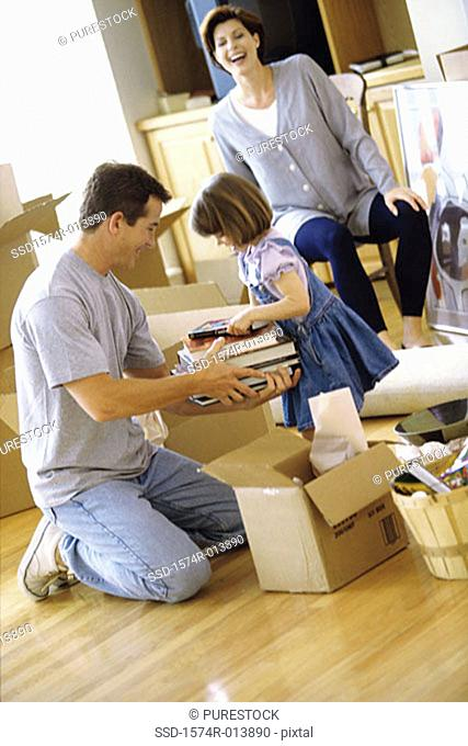 Father and daughter packing books in a cardboard box