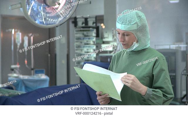 Lockdown, Medium Shot, Doctor wearing surgical scrubs and looking at a chart