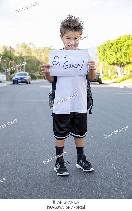 Portrait of schoolboy holding paper with handwritten school grade