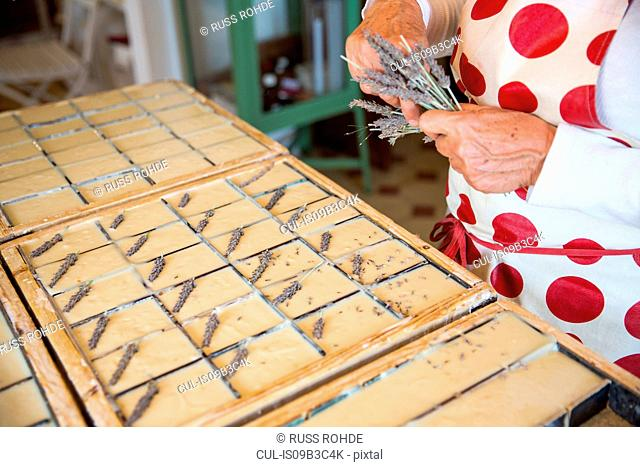 Mid section of woman applying dried lavender to soap bars in handmade soap workshop