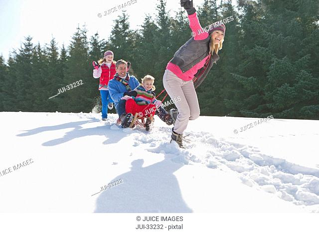 Happy family sledding in snow
