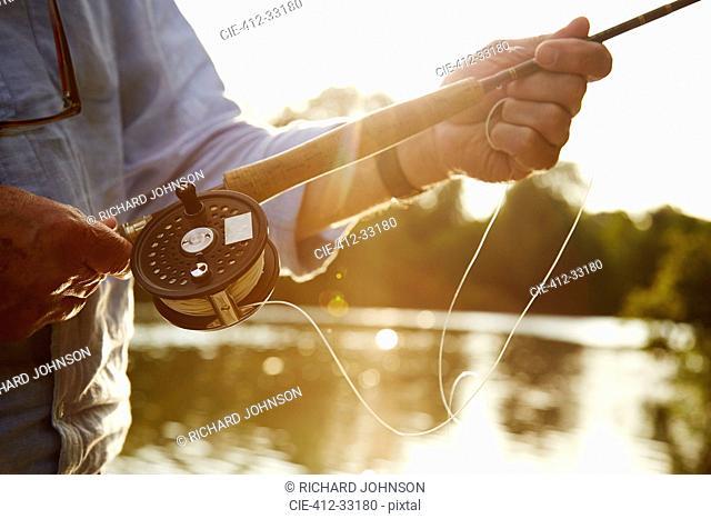 Close up senior man fly fishing at sunny river