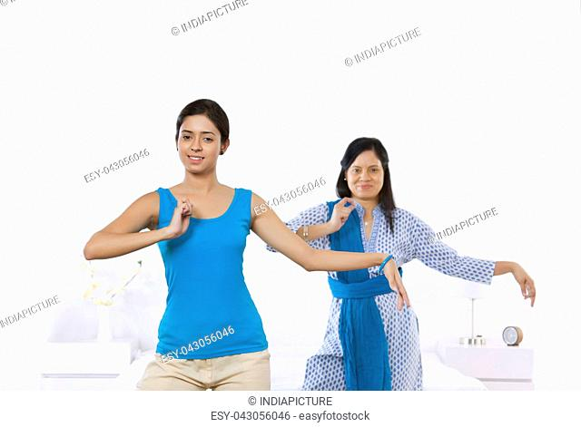 Portrait of mother and daughter in dance pose