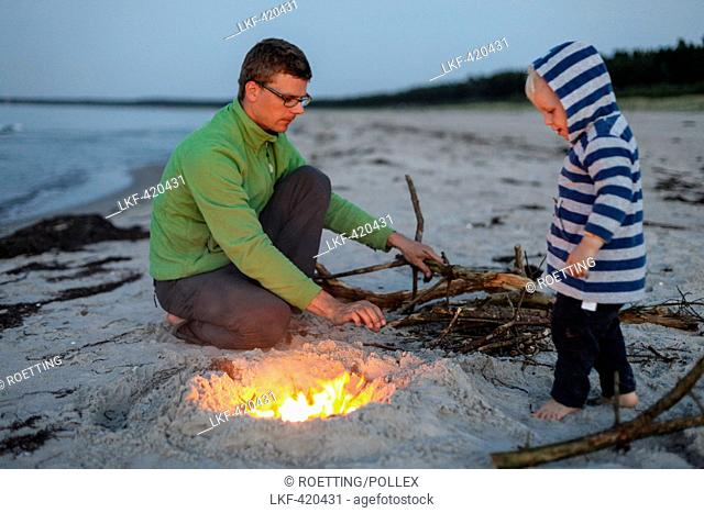 Father and son (2 years) at a campfire at beach in the evening, Schaabe, Island of Ruegen, Mecklenburg-Western Pomerania, Germany