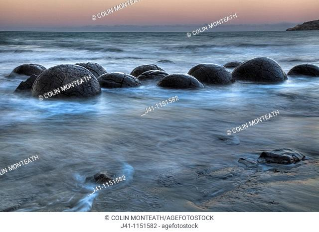Moeraki boulders at dusk, glow over Pacific Ocean, near Oamaru, Otago, New Zealand