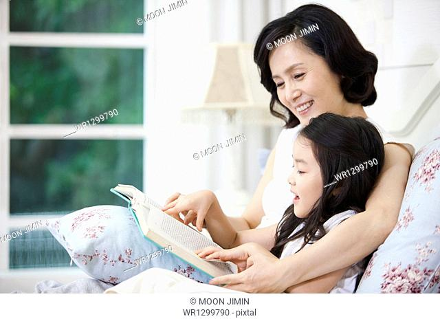 a woman and granddaughter reading a book together