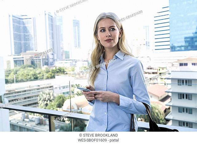 Blond woman with smartphone leaning agianst glass railing in the city
