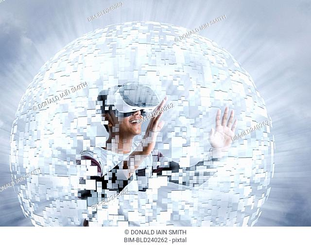Fiji Indian boy wearing virtual reality goggles in floating sphere