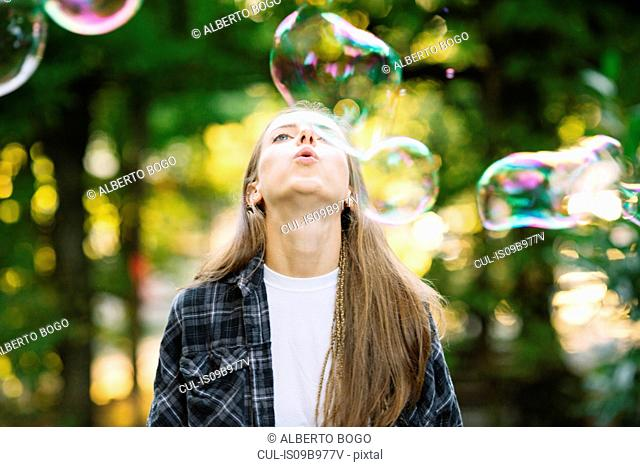 Young woman blowing floating bubble upwards in park