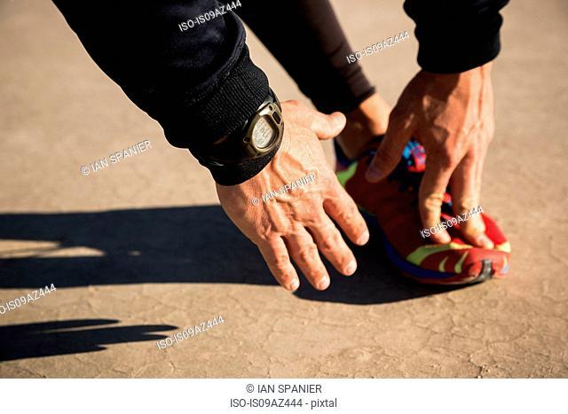 Cropped shot of man training, touching toes on dry lake bed, El Mirage, California, USA