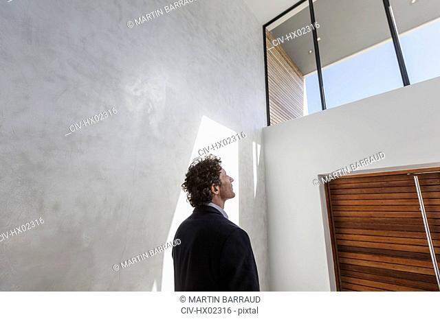 Pensive businessman looking up at window