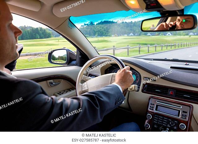 Businessman talking on cell phone while driving and overtaking, not paying attention to the road and traffic