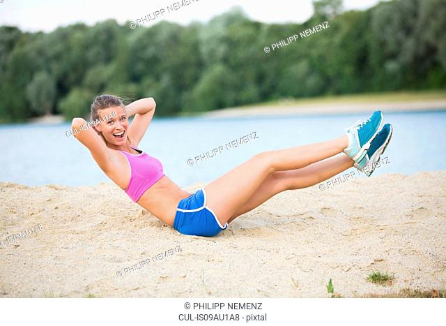 Young woman doing warm up exercises at lakeside