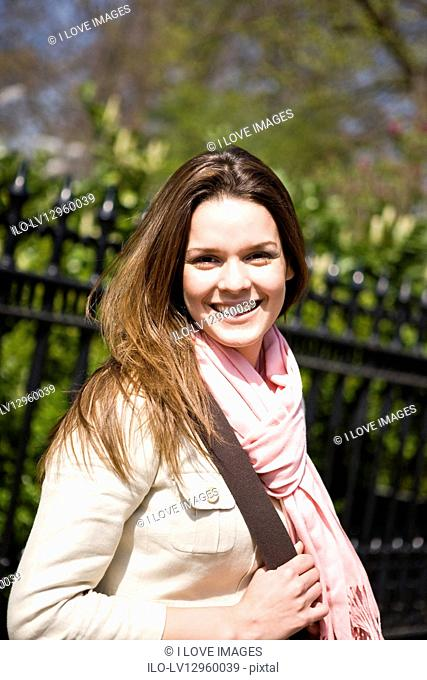 Portrait of a young woman smiling, outdoors