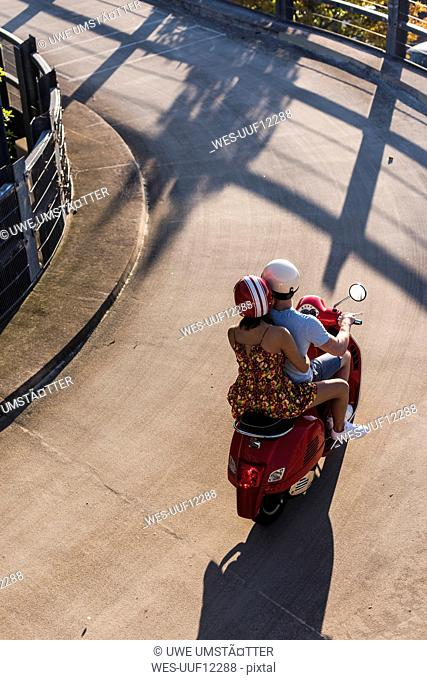 Bird's eye view of young couple riding motor scooter