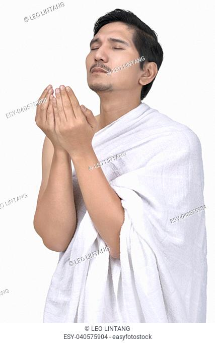 Religious asian muslim man with hajj cloth pray isolated over white background