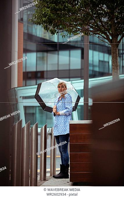 Beautiful woman holding umbrella and standing on street