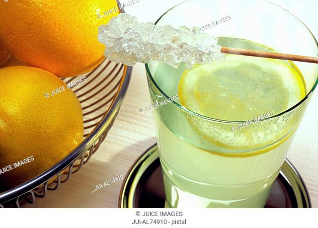 High angle view of a glass of lemonade with a sugar stirrer balanced on top