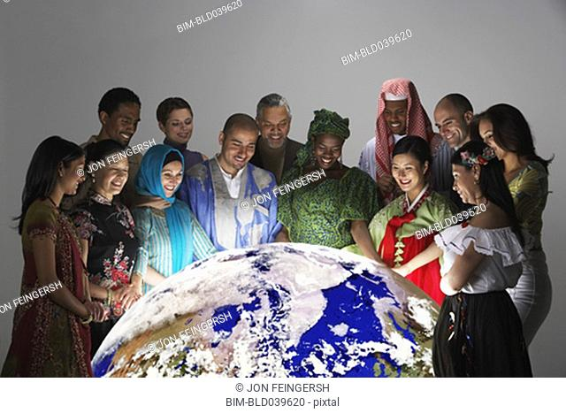Ethnic-ethnic people in traditional dress looking at globe