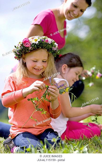 Kindergarten teacher picking flowers with children in a wood kindergarten