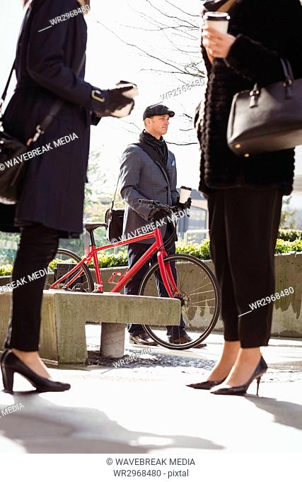 Businessman walking with his cycle while woman interacting with each other