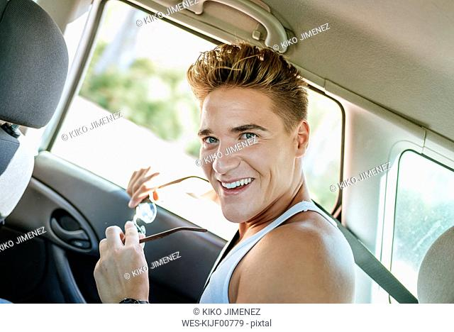Happy young man in a car
