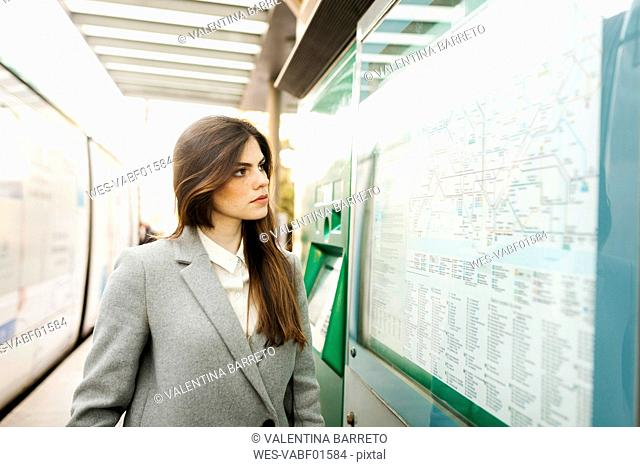 Spain, Barcelona, portrait of young businesswoman looking at map at station