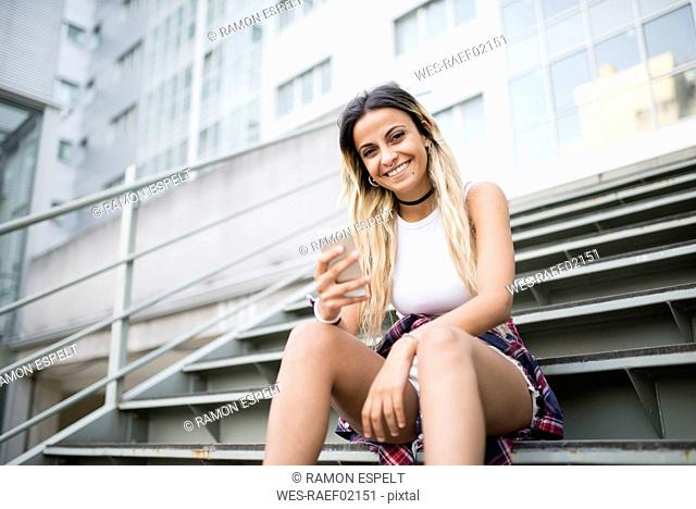 Young woman sitting on stairs, using smartphone